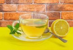 Τσάι με τη μέντα και λεμόνι σε μια κίτρινη επιφάνεια Στοκ Εικόνες