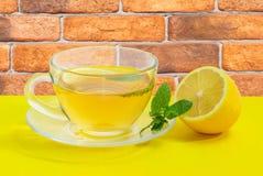 Τσάι με τη μέντα και λεμόνι σε μια κίτρινη επιφάνεια Στοκ Εικόνα