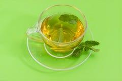 Τσάι με τη μέντα στο φλυτζάνι γυαλιού σε ένα πράσινο υπόβαθρο Στοκ εικόνα με δικαίωμα ελεύθερης χρήσης