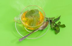 Τσάι με τη μέντα στο φλυτζάνι γυαλιού σε ένα πράσινο υπόβαθρο Στοκ Εικόνες