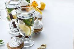 Τσάι με το λεμόνι και τη μέντα cupcakes με την κρέμα και τις κίτρινες τουλίπες Στοκ φωτογραφίες με δικαίωμα ελεύθερης χρήσης