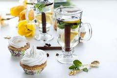 Τσάι με το λεμόνι και τη μέντα cupcakes με την κρέμα και τις κίτρινες τουλίπες Στοκ εικόνα με δικαίωμα ελεύθερης χρήσης