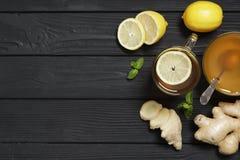 Τσάι με το λεμόνι και την πιπερόριζα, μέλι και μέντα σε ένα μαύρο ξύλινο υπόβαθρο στοκ φωτογραφίες
