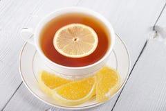 Τσάι με το λεμόνι σε ένα άσπρες φλυτζάνι και μια μαρμελάδα Στοκ Φωτογραφία