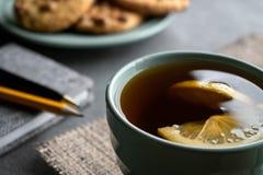 Τσάι με το λεμόνι, τα μπισκότα φυστικιών και το γκρίζο σημειωματάριο με το στυλό και το μολύβι στοκ εικόνες