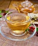 Τσάι με lingonberry στο φλυτζάνι γυαλιού στην πετσέτα μπαμπού Στοκ Εικόνες