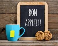 Τσάι, μπισκότα και πίνακας με τις επιθυμίες Bon appetit Στοκ Φωτογραφία