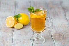 Τσάι πιπεροριζών λεμονιών στο γυαλί με τη μέντα και μέλι σε ένα άσπρο backgro Στοκ φωτογραφία με δικαίωμα ελεύθερης χρήσης