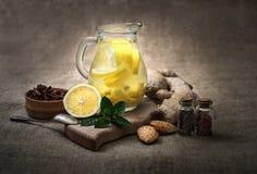 Τσάι πιπεροριζών με το λεμόνι, τη ρίζα πιπεροριζών και τη μέντα στο αγροτικό υπόβαθρο Στοκ Εικόνα