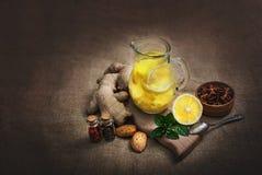 Τσάι πιπεροριζών με το λεμόνι, τη ρίζα πιπεροριζών και τη μέντα στο αγροτικό υπόβαθρο Στοκ Εικόνες
