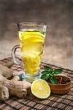 Τσάι πιπεροριζών με το λεμόνι, τη ρίζα πιπεροριζών και τη μέντα στο αγροτικό υπόβαθρο Στοκ Φωτογραφία