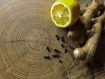 Τσάι πιπεροριζών με το λεμόνι και γαρίφαλα στον ξύλινο πίνακα στοκ φωτογραφία