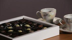 Τσάι που τίθεται στον πίνακα με την καραμέλα σοκολάτας απόθεμα βίντεο
