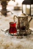 Τσάι που τίθεται στο ασιατικό ύφος διαμορφωμένο στο αχλάδι γυαλί με την εκλεκτής ποιότητας κατσαρόλα και τα φρούτα ημερομηνιών Στοκ Φωτογραφία