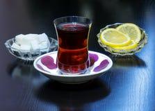 Τσάι που χύνεται σε ένα γυαλί Armud με το λεμόνι και τη ζάχαρη Στοκ Φωτογραφίες