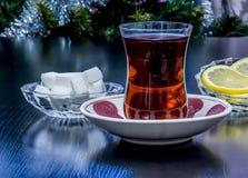 Τσάι που χύνεται σε ένα γυαλί Armud με το λεμόνι και τη ζάχαρη Στοκ Εικόνες