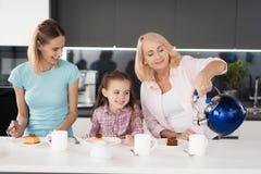 Τσάι πριν από το γεύμα για την ημέρα των ευχαριστιών Δύο γυναίκες και ένα κορίτσι που παίρνει έτοιμο να πιει το τσάι με μια σπιτι Στοκ Εικόνες