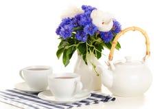 Τσάι προγευμάτων στον πίνακα με την μπλε και άσπρη ανθοδέσμη στην άσπρη πλάτη Στοκ φωτογραφία με δικαίωμα ελεύθερης χρήσης