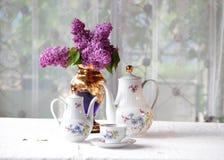 Τσάι σε ένα φλυτζάνι, και μια ιώδης ανθοδέσμη σε έναν πίνακα Στοκ εικόνα με δικαίωμα ελεύθερης χρήσης