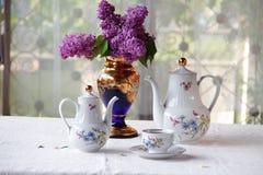 Τσάι σε ένα φλυτζάνι, και μια ιώδης ανθοδέσμη σε έναν πίνακα Στοκ φωτογραφίες με δικαίωμα ελεύθερης χρήσης