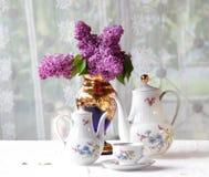 Τσάι σε ένα φλυτζάνι, και μια ιώδης ανθοδέσμη σε έναν πίνακα στοκ εικόνες με δικαίωμα ελεύθερης χρήσης