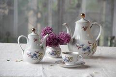 Τσάι σε ένα φλυτζάνι, και μια ιώδης ανθοδέσμη σε έναν πίνακα Στοκ Εικόνες
