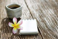 Τσάι στο παλαιό φλυτζάνι με το σημειωματάριο και plumaria στον ξύλινο πίνακα Στοκ Εικόνες
