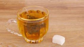Τσάι στο φλυτζάνι και ζάχαρη, κουτάλι στον πίνακα απόθεμα βίντεο
