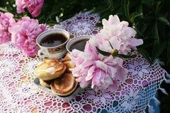 Τσάι στο ύφος χωρών στο θερινό κήπο Δύο φλυτζάνια του μαύρων τσαγιού και των τηγανιτών στο χειροποίητο πλεγμένο εκλεκτής ποιότητα στοκ φωτογραφία με δικαίωμα ελεύθερης χρήσης