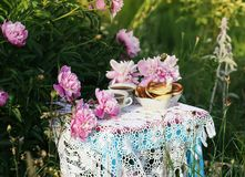 Τσάι στο ύφος χωρών στο θερινό κήπο Δύο φλυτζάνια του μαύρων τσαγιού και των τηγανιτών στο χειροποίητο πλεγμένο εκλεκτής ποιότητα στοκ φωτογραφίες