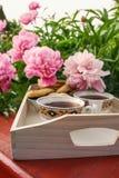 Τσάι στο ύφος χωρών στο θερινό κήπο στο χωριό Δύο φλυτζάνια του μαύρου τσαγιού στον ξύλινο δίσκο και τα ανθίζοντας peony λουλούδι στοκ εικόνα με δικαίωμα ελεύθερης χρήσης