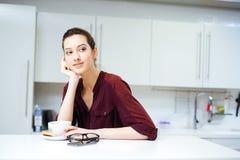 Τσάι συνεδρίασης και κατανάλωσης γυναικών χαμόγελου στην κουζίνα Στοκ φωτογραφία με δικαίωμα ελεύθερης χρήσης