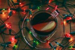 Τσάι της Apple σε έναν ξύλινο πίνακα στο φλυτζάνι γυαλιού μεταξύ της γιρλάντας Στοκ εικόνα με δικαίωμα ελεύθερης χρήσης