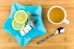 Τσάι, φέτες του λεμονιού, άμορφη ζάχαρη στο μπλε πιάτο Στοκ Εικόνες