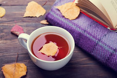 Τσάι, φύλλα φθινοπώρου και κάλυμμα στον ξύλινο πίνακα στοκ φωτογραφία
