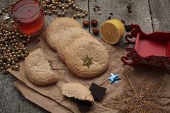 Τσάι Χριστουγέννων με τα μπισκότα, τα παιχνίδια Χριστουγέννων και τα γλυκά, λεμόνι, χρυσές χάντρες, Στοκ Εικόνες