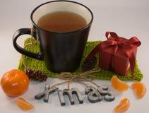 Τσάι Χριστουγέννων σε ένα μαύρο φλυτζάνι, ένα μανταρίνι και ένα κόκκινο κιβώτιο δώρων σε ένα whi Στοκ Εικόνα