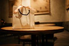 Τσάντα εγγράφου εορτασμού με τη θέση κορδελλών στον ξύλινο πίνακα στο restaur Στοκ φωτογραφία με δικαίωμα ελεύθερης χρήσης