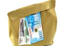 Τσάντα εγγράφου με τα χρήματα στο άσπρο υπόβαθρο στοκ φωτογραφίες