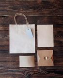 Τσάντα εγγράφου προτύπων από το έγγραφο του Κραφτ με τα κιβώτια δώρων ετικεττών και Χριστουγέννων δώρων σε ένα ξύλινο υπόβαθρο Στοκ Εικόνες