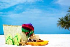 Τσάντα θερινών παραλιών με το κοράλλι, την πετσέτα, τα γυαλιά ηλίου και το κοράλλι στην αμμώδη παραλία Στοκ Φωτογραφίες