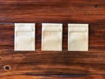 3 τσάντα κλειδαριών φερμουάρ εγγράφου της Kraft στον εκλεκτής ποιότητας ξύλινο πίνακα στοκ φωτογραφίες με δικαίωμα ελεύθερης χρήσης