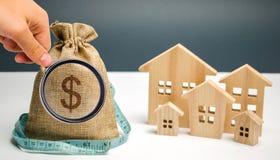 Τσάντα με το σημάδι χρημάτων και δολαρίων και ξύλινα σπίτια με το μέτρο ταινιών Περιορισμένος προϋπολογισμός πόλεων Επένδυση των  στοκ φωτογραφίες