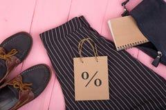 τσάντα, παντελόνι, παπούτσια, τσάντα δώρων με το σημάδι έκπτωσης, σημειωματάριο στο ρόδινο ξύλινο υπόβαθρο Στοκ Εικόνες