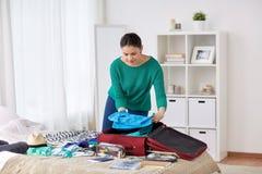 Τσάντα ταξιδιού συσκευασίας γυναικών στο σπίτι ή δωμάτιο ξενοδοχείου Στοκ Εικόνες
