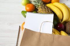 Τσάντα Aper των διαφορετικών φρούτων με το σημειωματάριο στο άσπρο ξύλινο υπόβαθρο Στοκ Εικόνες