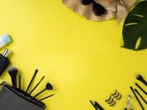Τσάντα Makeup με την ποικιλία του κίτρινου υποβάθρου προϊόντων ομορφιάς στοκ εικόνα