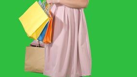 Τσάντες αγορών εκμετάλλευσης γυναικών στα χέρια της και παραγωγή να ανοίξει μια πράσινη οθόνη, κλειδί χρώματος απόθεμα βίντεο