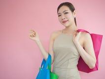 Τσάντες εκμετάλλευσης γυναικών αγορών στο ρόδινο υπόβαθρο, ασιατικό κορίτσι Στοκ Φωτογραφίες