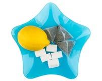 Τσάντες λεμονιών, ζάχαρης και τσαγιού στο μπλε πιάτο γυαλιού Στοκ φωτογραφία με δικαίωμα ελεύθερης χρήσης